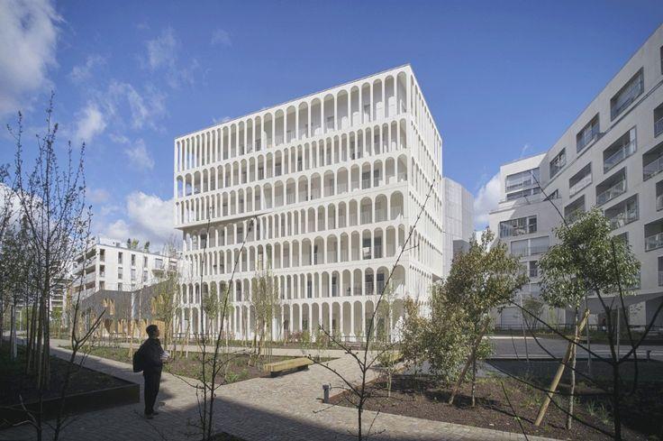 Dove un tempo sorgevano le enormi fabbriche Renault a Parigi, Antonini Darmon ha disegnato 33 case popolari in un edificio di cemento bianco caratterizzato da una lunga serie di archi scenografici.