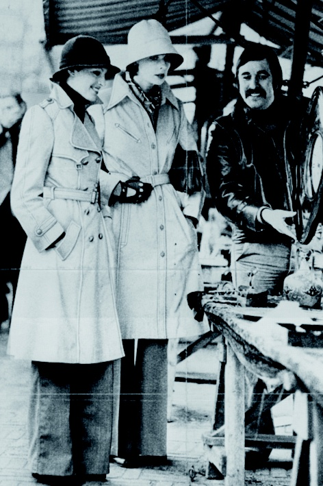 Seventies fashion: models in trenchcoats, leather gloves and flared pants.