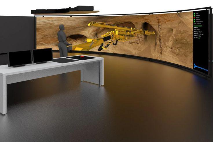 Schulungsumgebung mit Multi Screen Projection. Eine 3 x 9 Meter große Projektionswand lässt Schulungsteilnehmende in die Simulation eines Bohrwagens unter Tage eintauchen. Der Simulator wird mit originalgetreuer Funk-Fernsteuerung bedient. Der digitale Zwilling lässt Auszubildende Bohrhauer alle Funktionen des Bohrwagens erleben.