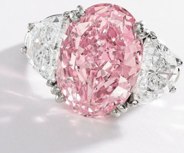 Pink diamond and diamond ring, Oscar Heyman and Bros. Center stone: an oval-shaped Fancy Intense Pink diamond weighing approximately 6.54 carats, flanked by 2.21 carats of white diamonds. Via Diamonds in the Library.