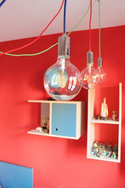Particolare del lampadario con cavi colorati e semplici bulbi.
