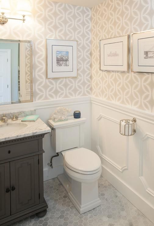 Chic powder room features top half of walls clad in beige geometric wallpaper and lower walls clad in decorative moldings lined with a gray vanity