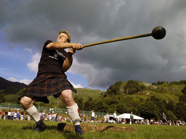 A kilted contestant twirls and hurls a heavy burden during a hammer throw event in Glenfinnan. Traditional highland games feature a heady mix of dance, drink, and food to complement feats of athletic prowess.