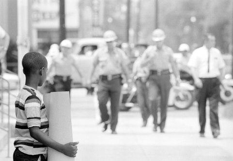 Deputies approach child demonstrator in front of the Dallas County courthouse Selma, Alabama, July 8, 1964  Photography by Matt Herron