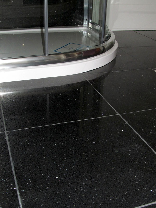 Quartz Tiles - Black. These stunning, sparkling Black Mirror Quartz floor tiles will impress your guests for sure. The surface has a highly gloss finish, with sparkling specks of mirror trapped inside the tile.  We have six stunning colours for you to choose from.