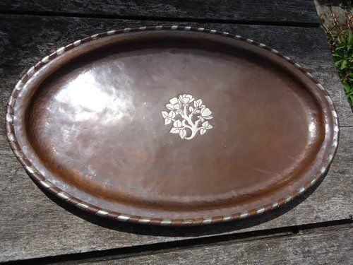 Arts & Crafts oval copper tray with an inlaid pewter flowers to centre with raised pattern rim. Offered in excellent original condition with no loss of pewter to ship. It has the impressed mark of HW for Hugh Wallis coppersmith of Altrincham (1871 -1943)