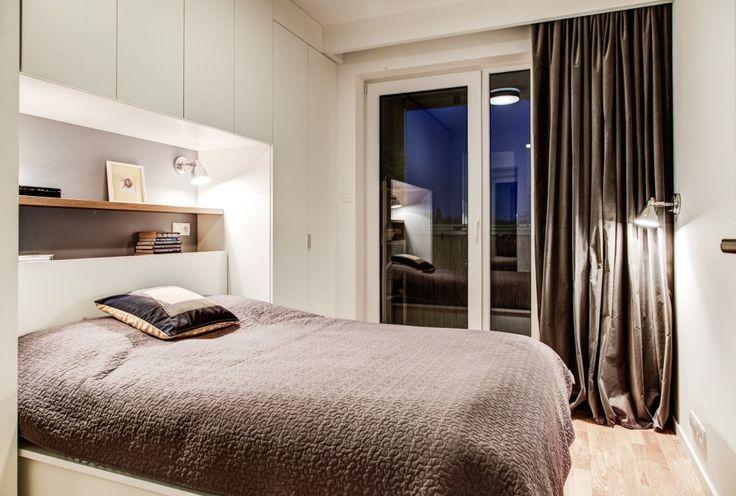 Aranżacja sypialni w nowoczesnym stylu, gdzie system szaf nie znajduje się naprzeciw łóżka, tylko stanowi zabudowę ponad nim.