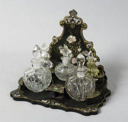 Nécessaire à parfum en carton bouilli laqué noir et or burgauté avec cinq flacons (un bouchon changé). Epoque Napoléon III.