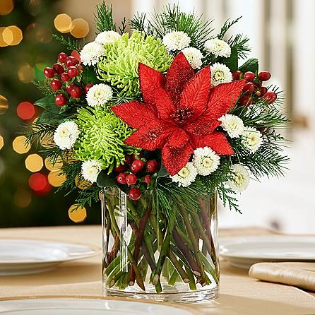 Season's Greetings Centerpiece - The holidays are all about warm welcomes and joyous celebrations. Send a gift of merriment with this festive centerpiece featuring beautiful white poms, red hypericum, fragrant greens and a red glitter faux poinsettia.