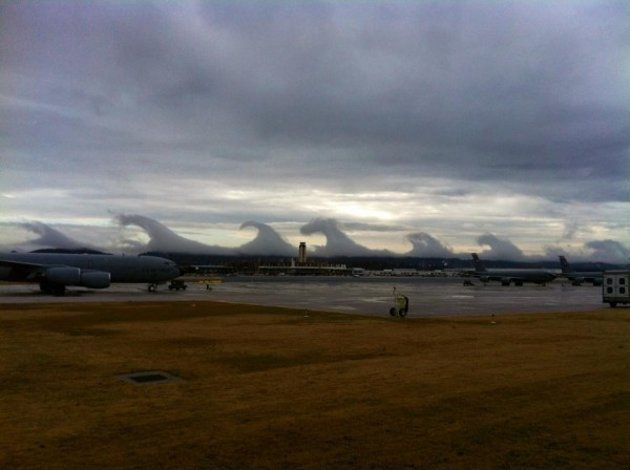 """A series of huge breaking waves line the horizon in Birmingham, AL, 12/16/2011,  their crests surging forward in slow motion.  Experts say the clouds were pristine examples of """"Kelvin-Helmholtz waves."""" Whether seen in the sky or in the ocean, this type of turbulence always forms when a fast-moving layer of fluid slides on top of a slower, thicker layer, dragging its surface."""