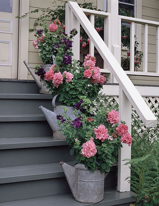 Galvanized watering cans line the porch steps.....love this  : )