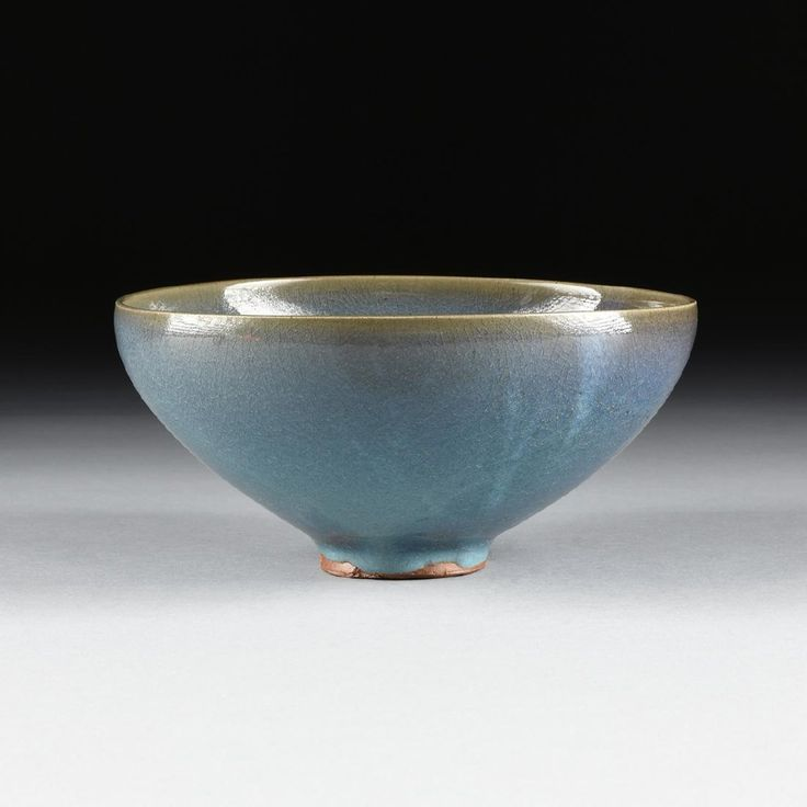CHINESE SONG DYNASTY STYLE JUNYAO GLAZED EARTHENWARE BOWL, the yellowed rim over a pale milky blue and lavender hued surface, dotted by a single mark of deep purple, raised on a circular foot.