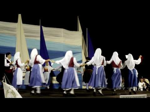 "Kefalonia dance video. Men wear black vests, burgundy vraka. Women wear burgundy vests, ""Swedish"" blue skirts."