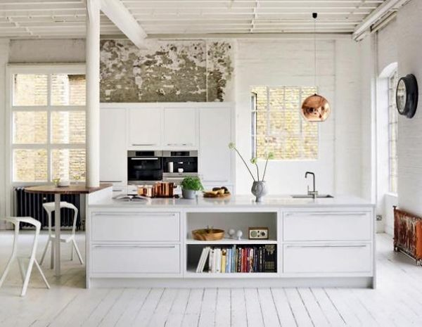 White Kitchen With Exposed Brick Wall, White Cabinetry, Kitchen Island And  Copper Pendant Light