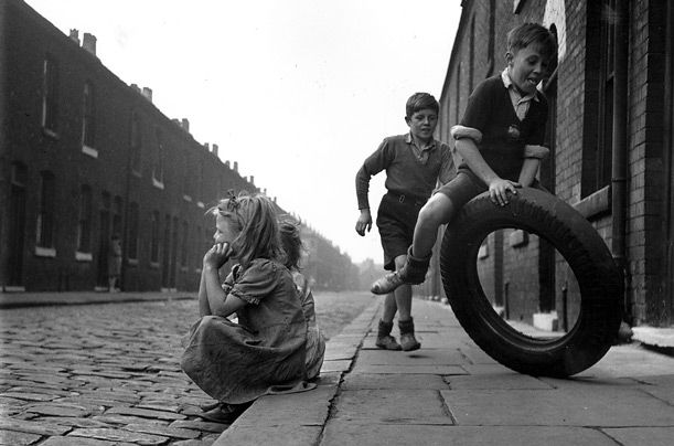 Children playing with an old tyre on the streets of Salford, Manchester, 1951