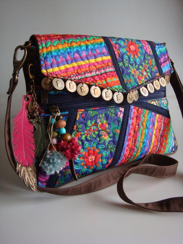 Bolsa de lona com a parte da frente feita de algodão, quiltada em manta acrílica. Possui bolsos na frente, na parte de trás e internamente. Alça transversal