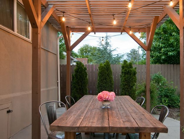 A strand or two of outdoor café lights (the kind with large bulbs and exposed filaments) is a can't-miss way to bring life to an outdoor seating area. If you do not have access to outlets, hang solar-powered string lights instead. #patios #interiordesign #cafelights #patiodecor #outdoorspaces #outdoorseatingarea