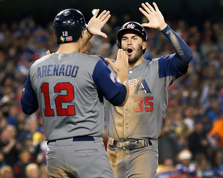 The United States' Nolan Arenado (12) and Eric Hosmer (35) celebrate after scoring on a seventh-inning single by Brandon Crawford against Puerto Rico in the World Baseball Classic championship at Dodger Stadium in Los Angeles on Wednesday, March 22, 2017.