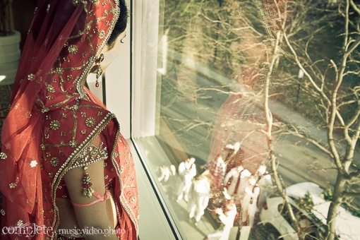 Indian bride watching the baraat via IndianWeddingSite.com