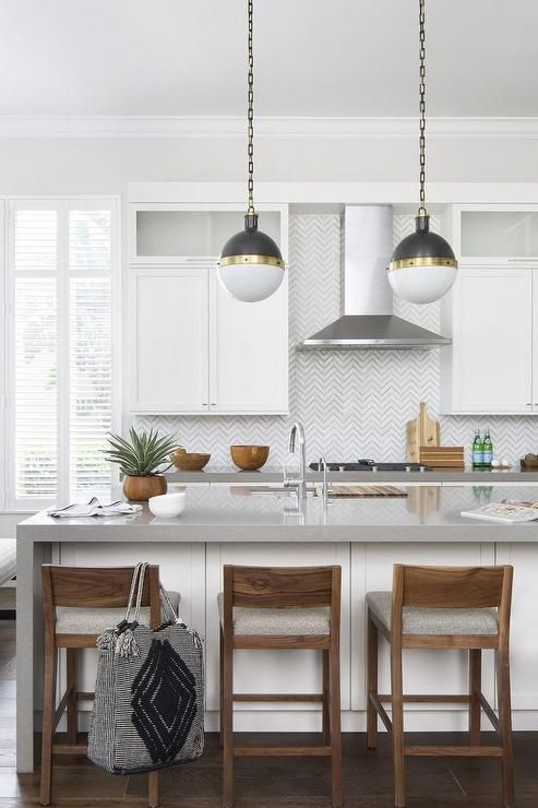 Beautifully appointed white and gray kitchen boasts wood counter stools placed in front of a white island topped with a gray quartz waterfall countertop finished with a sink and polished nickel gooseneck faucet lit by two Small Hicks Pendants.