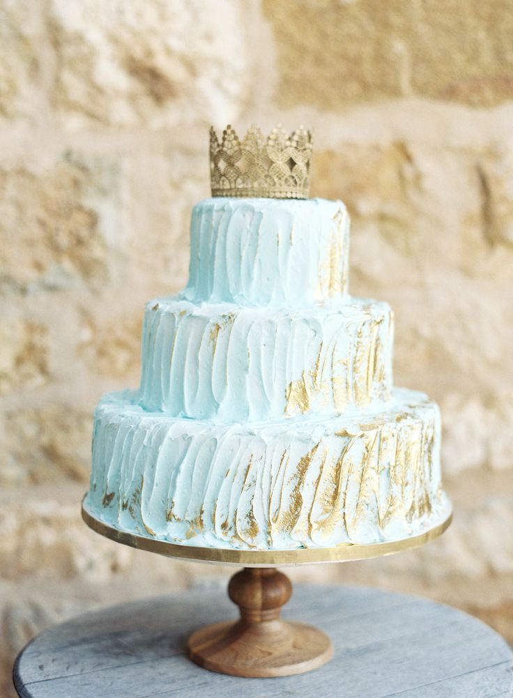 We're not sure what we love most about this pastel creation—the pale-blue icing, the gold detailing, andthe regal crown topper are all stunning.