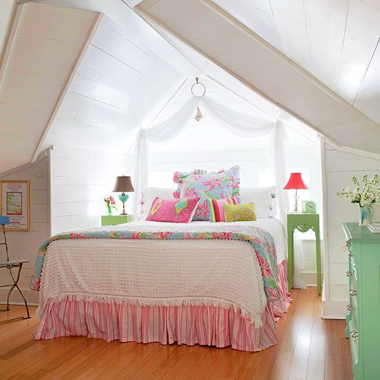 With low ceilings and awkward angles, attic bedrooms often present decorating challenges. Here, the attic walls were given a coat of glossy white paint to ensure maximum light reflection from the limited windows. Pops of pastel pinks, blues, and greens give the space youthful energy.