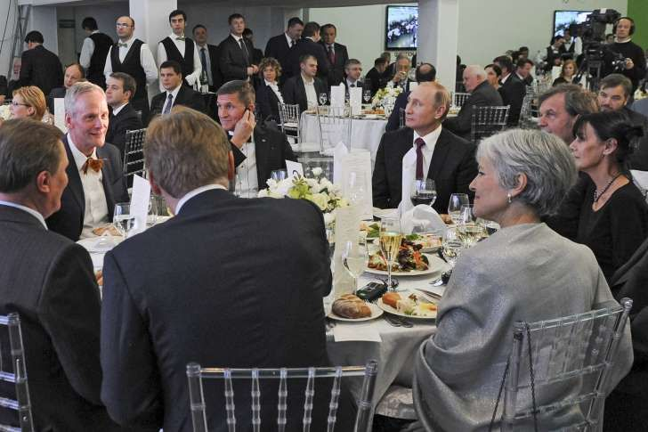 a group of people sitting at a table in front of a crowd: Russian President Vladimir Putin (center right) with retired U.S. Lt. Gen. Michael T. Flynn (center left) and former Green Party presidential candidate Jill Stein (front right) attend an exhibition marking the 10th anniversary of RT (RussiaToday) 24-hour English-language TV news channel in Moscow on Dec. 10, 2015.