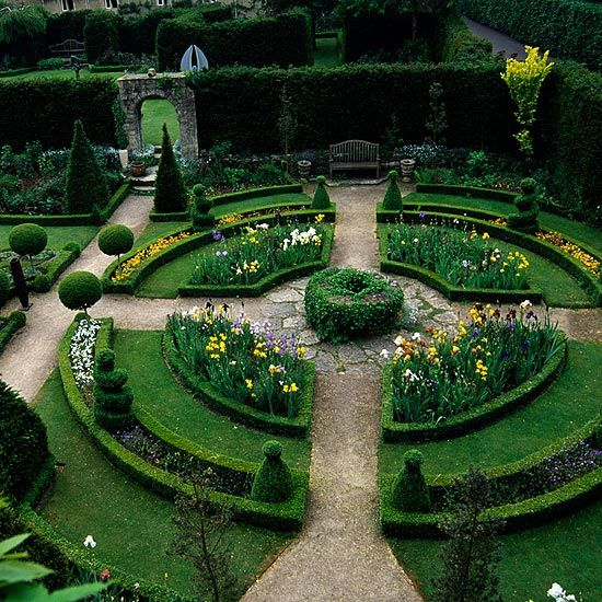 Abbeey House in Wiltshire. Round garden with a geometric shape, carefully pruned hedges, and symmetrical colors. #gardendesign