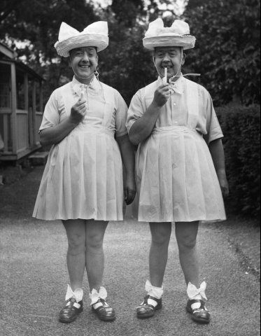 """The """"lovely"""" Primwaddle Twins, Mort and Harvey, circa 1929. Their mother, Discordia's husband left after seeing the homely pair. Embittered to men, left alone to raise boys, she insisted they were girls, and got away with it home-schooling them for 17 years; until Mort learned otherwise. The teenagers murdered her in her sleep, strangled in chiffon, here eyes gouged out and replaced with doll eyes."""