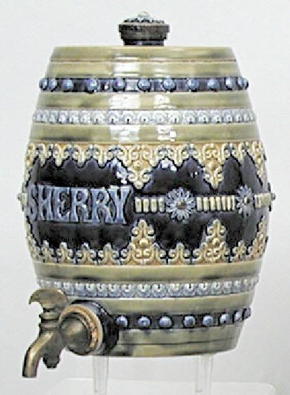 "A Doulton Lambeth Pottery Sherry Barrel. This beautiful barrel features deep blue background with light brown filigree decoration surrounding the center strip which features the raised letters ""SHERRY"" The top and bottom rimsare of medium green color and feature a band of light blue raised flower type design and a second band of dark blue beaded design.Also included is the original brass spigot. Signed Jonh Huskinson, England,circa 1801-1900"