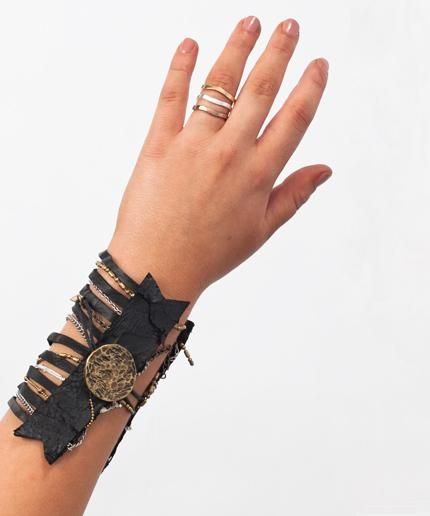 Distressed black leather cuff with beaten brass button closure and mixed metal chains.  Amazing statement piece.