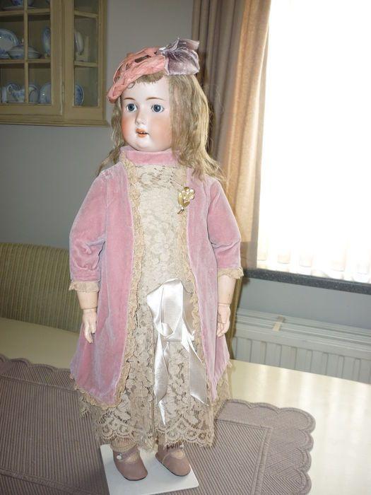 Deze grote pop  is zonder haar lijntjes. Haar lijf is in goede bespeelde staat , de onderbenen en enkele vingertjes zijn gerestaureerd.Zie foto's, zij zijn een onderdeel van de beschrijving. De pop heeft  vaste blauwe glazen ogen en haar originele mohair pruik. Mooie kleding naar oud model in velours en oude kant.
