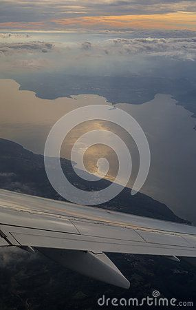 High up view on sunset over Lake Garda (Italy) and airplane winglet from porthole. Photo was made during the flight from Charles de Gaulle Airport (Paris, France) to Verona Villafranca Airport (Verona, Italy).