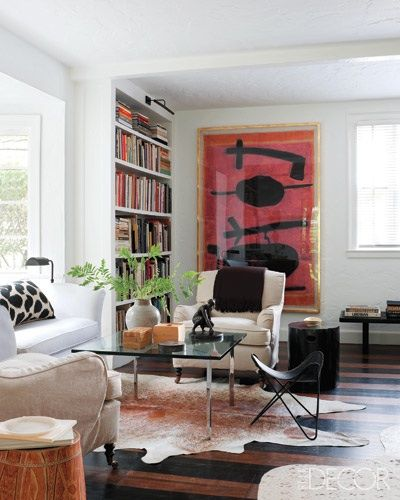 Doug Turshen's living room. Like the bold art. and the cozy book case.  Elle Decor.