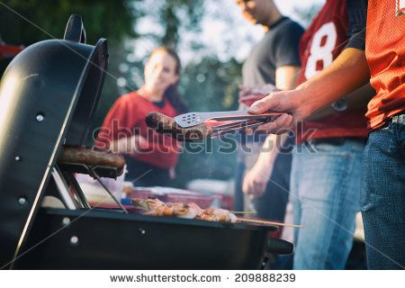 Tailgate: Man Works The Grill At Tailgating Party - stock photo