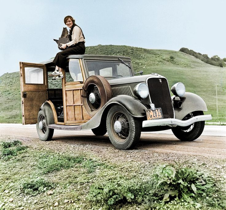 Dorothea Lange, Resettlement Administration photographer, in California atop her 1934 ford model 40 woodie with her giant camera. February 1936.