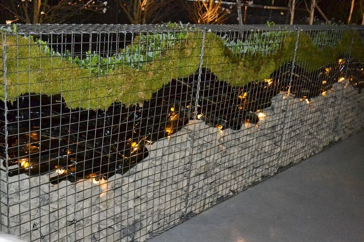 completed gabion wall with 1000 empty wine bottles