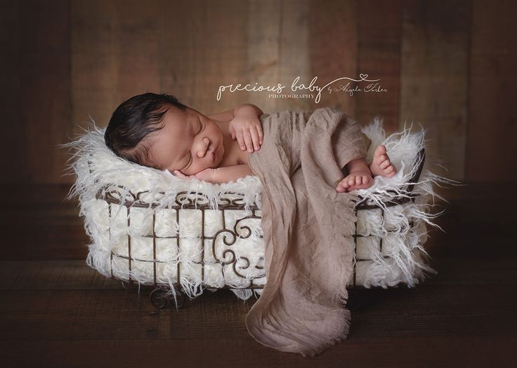 Gorgeous african american baby boy sleeping on fur in a basket newborn precious baby photography