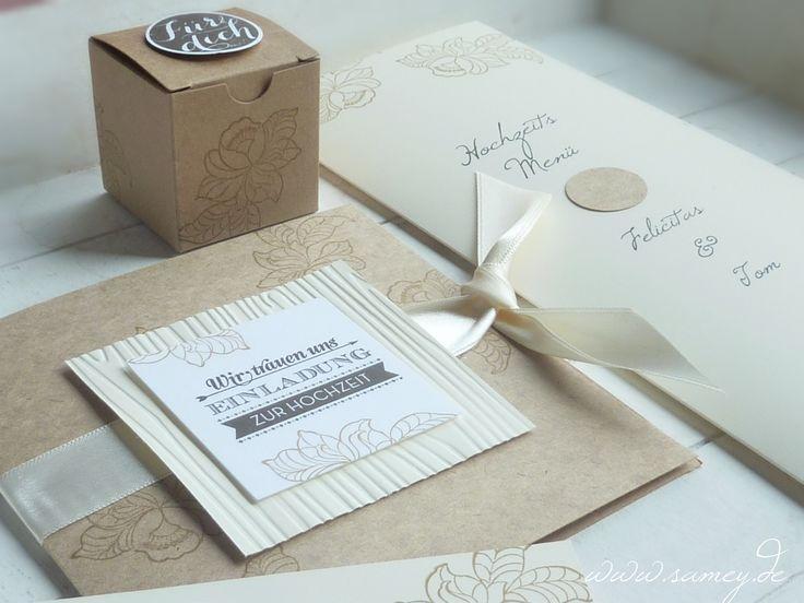 rustikale Hochzeitseinladung aus Kraftkarton, Satinband, Papierprägung und bestempeltem floralen Motiv;