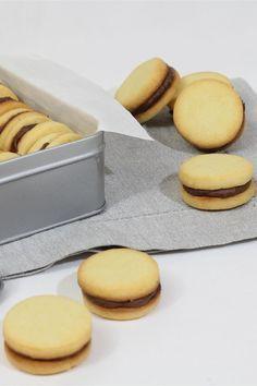 Questi squisiti biscotti ripieni al cioccolato sono dei frollini friabili di pasta frolla uniti da uno strato di crema al cioccolato preparata con del cioccolato al latte e formaggio light per una versione più leggera e cremosa.