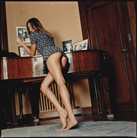 Helmut Newton - Carla Bruni with Family Photos, at home in Cavalière, France, 1992. Taken for Vanity Fair.