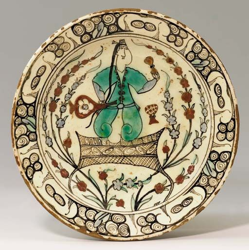 AN IZNIK POTTERY DISH Ottoman Turkey, circa 1630 With sloping rim in short foot, the white interior painted in bole-red, pale blue and turquoise green with a central human figure seated on a stylised rug holding a wine bottle in one hand and a glass in the other, a drum visible in the background, flanked by floral sprays, in a stylised wave and scroll border, the exterior with simple alternating flowerheads, rim chips, otherwise intact 11in. (28cm.) diam.