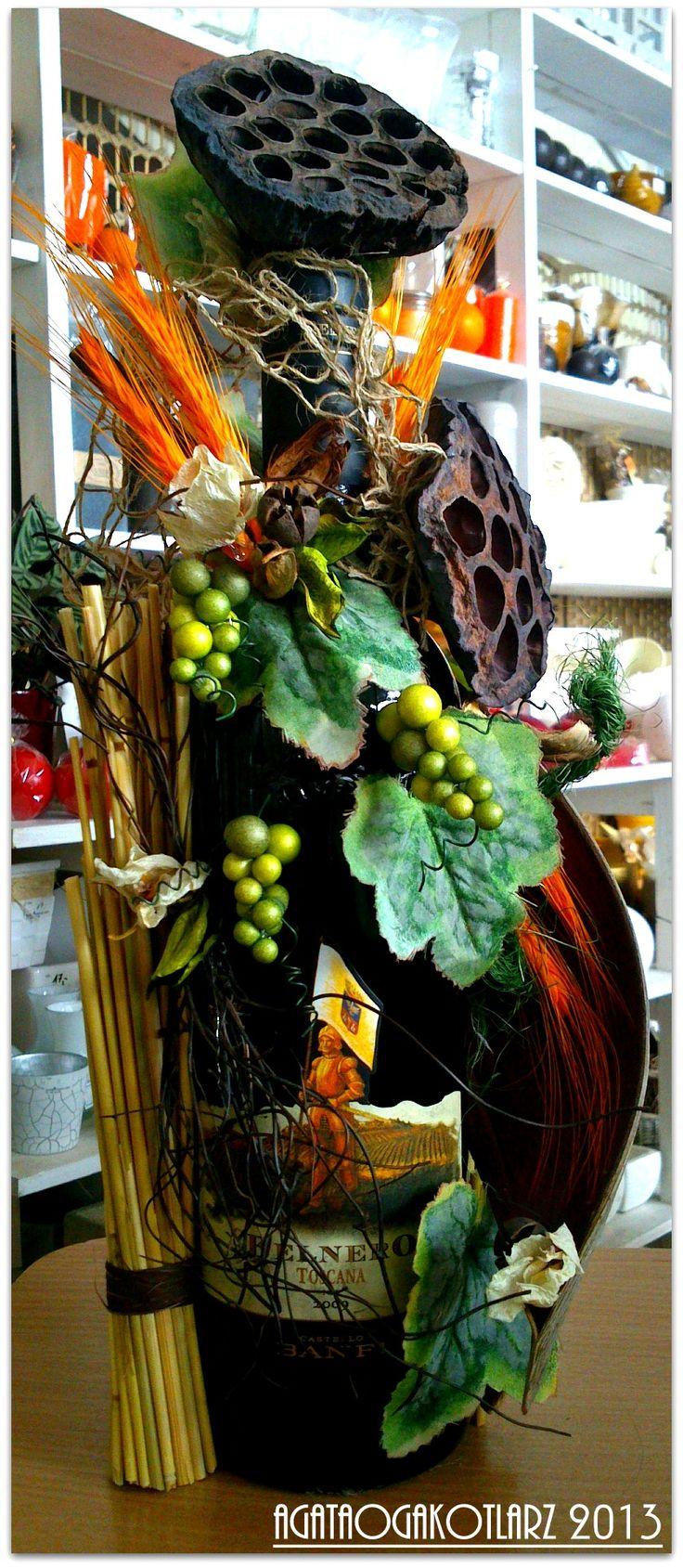 Butelka wina otoczona suszonymi kwiatami,owocami,sztucznymi liśćmi,maleńkim winogrono oraz słomą.