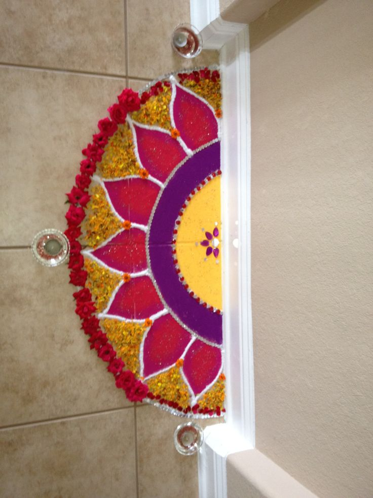 Rangoli using mirrors, colors, glitter and flower petals.