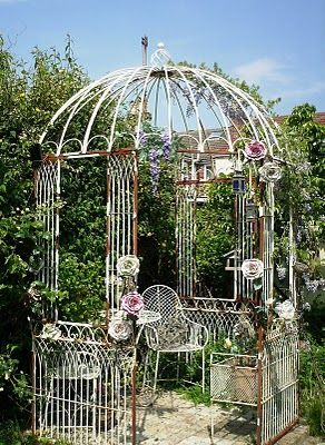 love this chippy white iron pergola...