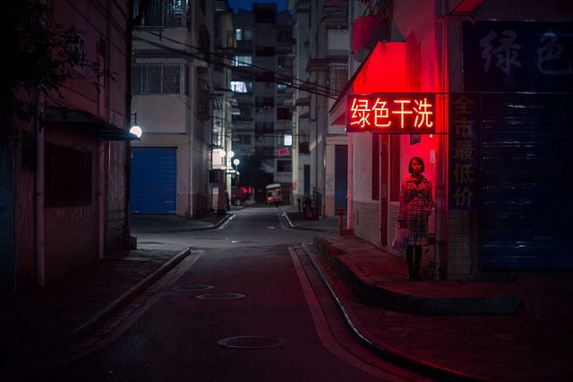 Photo of the Day: Alone on a Street Corner in China |A woman stands under a red neon sign, in an empty street in Guilin, #China on November 13, 2013. (金喜 刘/Flickr)