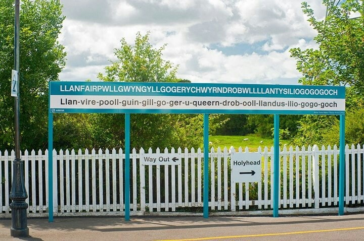 """Llanfair PG: """"The Welsh have a happy habit of running words together. Taken to an extreme, this gives Britain's longest railway station name sign at Llanfairpwllgwngyllgogerychwyndropwlllantysiliogogogoch. It may usually be seen with tourists being photographed alongside, and is often shortened to Llainfair PG."""" www.bradtguides.com"""