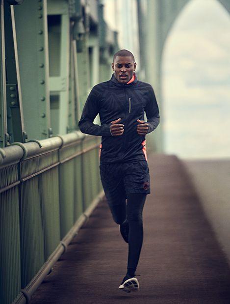 Il porte un pull noir et orange, des shorts noirs, des pantalons de jogging noirs et des baskets noirs.