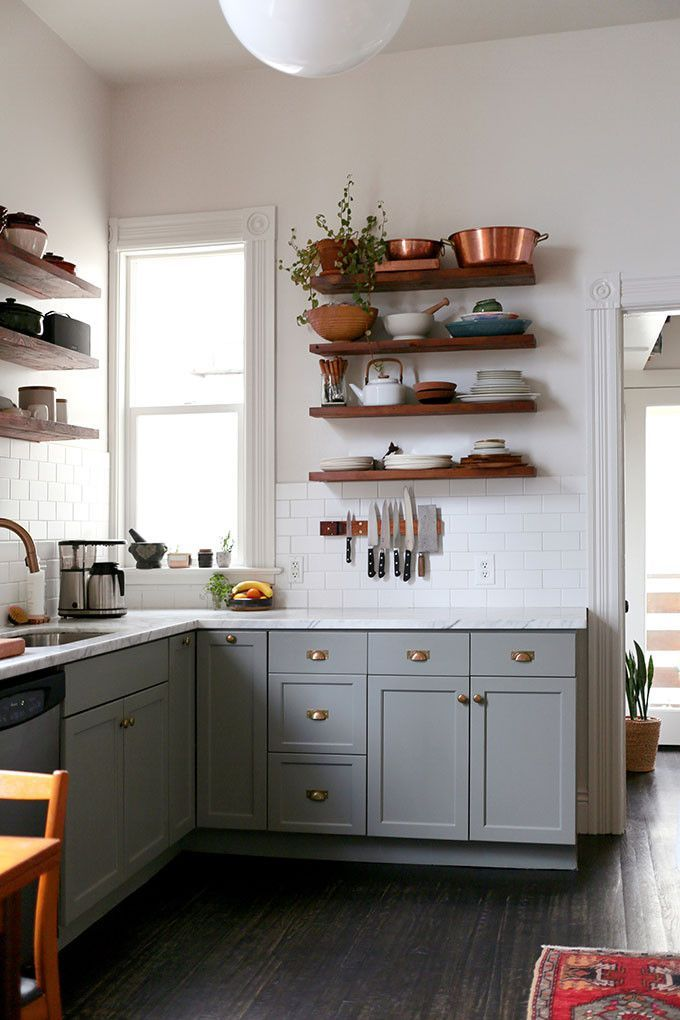 A pretty small kitchen with light gray cabinets, brass hardware, wood open shelving, and styling with copper.