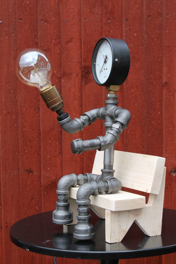Pipelight figure sat on a simple wooden bench made by Pipelightuk